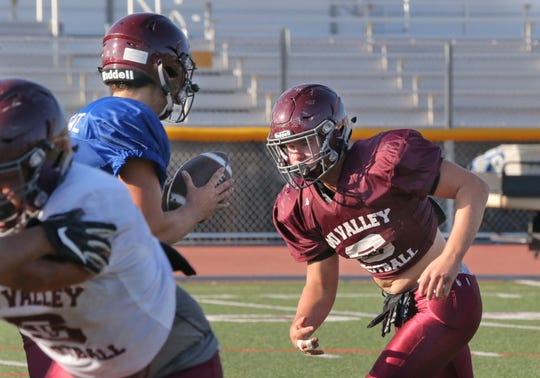 Simi Valley High running back Sean Weber takes the handoff from quarterback Jack Applegate during a recent practice.