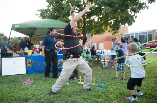 Senior Parole Officer James Jones of the New Jersey State Parole Board leads a hula hoop contest during the Vineland Police National Night Out event  held at the Vineland High School complex on Tuesday, August 7, 2018.