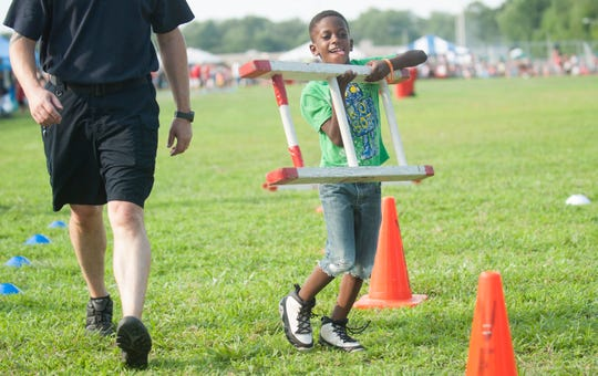 Rashaun Holley, 6 of Bridgeton, runs through a firefighter challenge obstacle course during the Vineland Police National Night Out held at the Vineland High School complex on Tuesday, August 7, 2018.