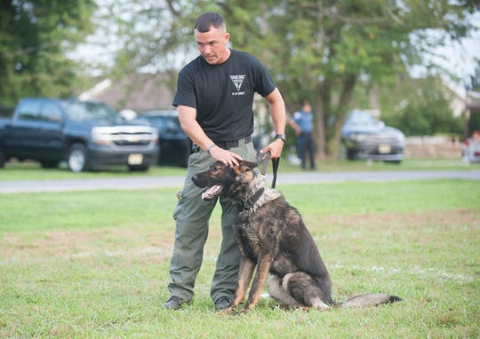 """Vineland Police K-9 Officer Derrick Magee stands with his K-9 partner Fifa moments before Fifa received a body armor vest, purchased through The Daily Journal community-funding project, """"Pennies for Puppies"""",  during the Vineland Police National Night Out event held at the Vineland High School complex on Tuesday, August 7, 2018."""