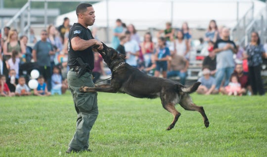 Vineland Police K-9 Officer Johnathan Ramos and his K-9 partner Rexo take part in a K-9 demonstration   during the Vineland Police National Night Out held at the Vineland High School complex on Tuesday, August 7, 2018.
