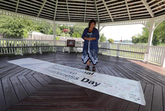 Lauren Privitera of Mahopac looks at a banner that she created to help mark International Overdose Awareness. Priviterxa's son Nicholas died of a heroin overdose in the 2014 at the age of twenty-three. For International Overdose Awareness Day, Privitera, will hold a  prayer vigil in the gazebo at Chamber Park on Lake Mahopac at 6:00 pm on Aug. 31st. This will be the third year that she has led the vigil.