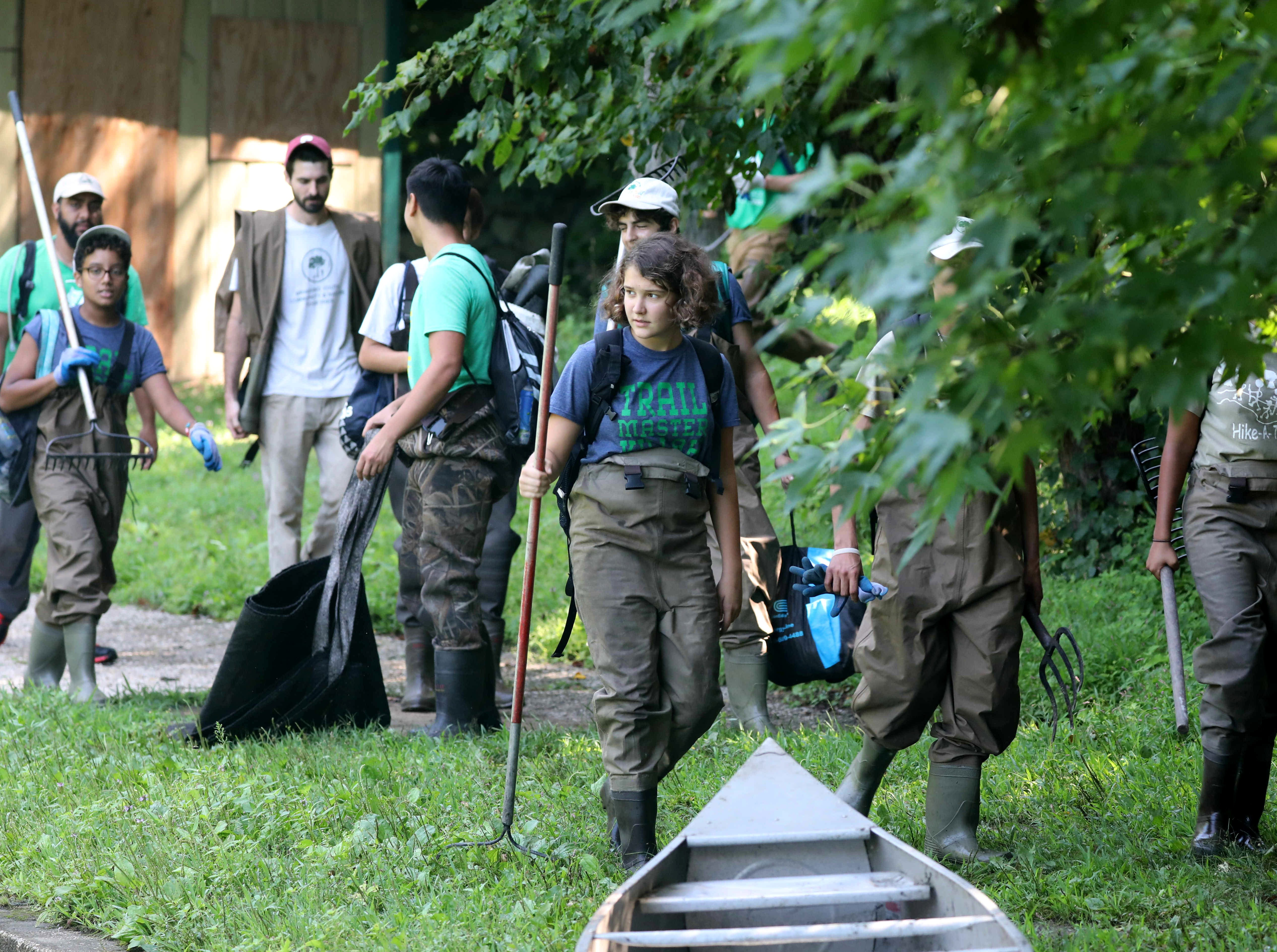 Volunteers with Friends of Van Cortlandt Park and Groundwork Hudson Valley arrive to assist The Westchester Parks Foundation collect some invasive water chestnut plants from the lake at Tibbetts Brook Park in Yonkers, Aug. 8, 2018.