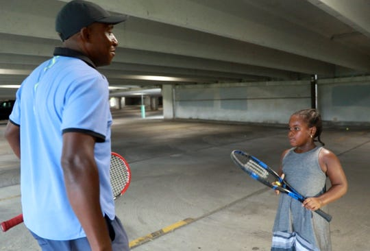 Kela Simunyola, operator of the Mount Vernon Tennis Center gives techniques with his student, Mali Cerease, 6, in the garage of Best Buy in Mount Vernon Aug. 7, 2018.