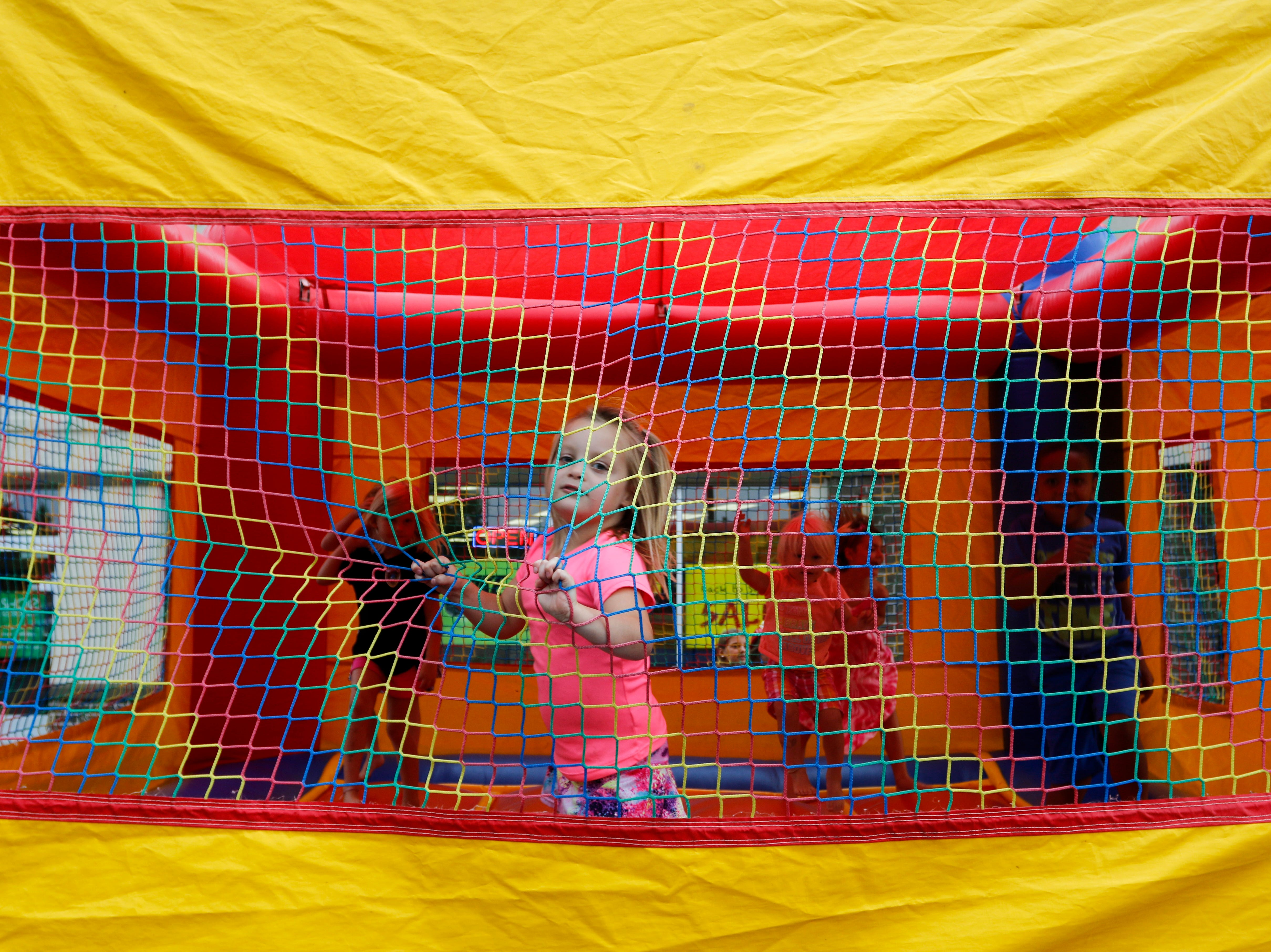 Alayna Mazurek, 4, plays in the bounce house during the National Night Out event put on by the Wisconsin Rapids Police Department in the Crossview Church parking lot in Wisconsin Rapids Tuesday, August 7, 2018.