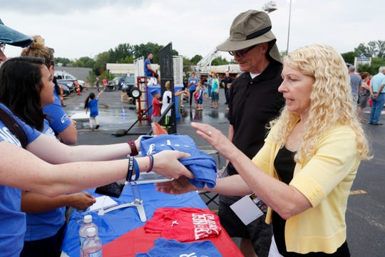 Andy and Brenda Dewitt purchase battle of the badges shirts during the National Night Out event put on by the Wisconsin Rapids Police Department in the Crossview Church parking lot in Wisconsin Rapids Tuesday, August 7, 2018. Red, blue and purple shirts were sold as part of a friendly competition between local law enforcement and fire fighters to raise money for the Fly High Memorial Playground.
