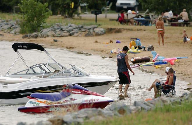 People hang out at the Lake Arrowhead beach Saturday, July 22, 2014.