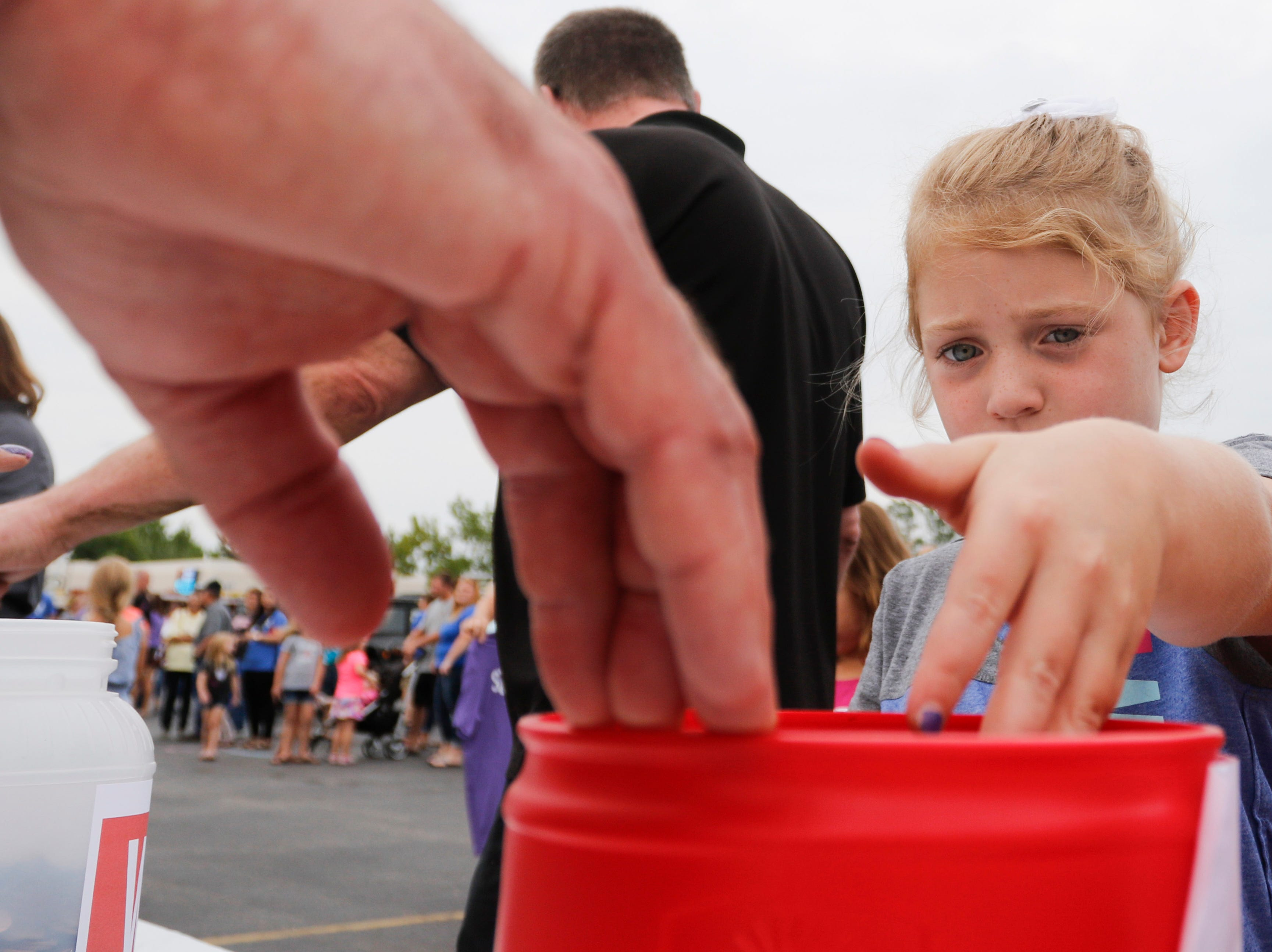 A girl donates change to the penny war during the National Night Out event put on by the Wisconsin Rapids Police Department in the Crossview Church parking lot in Wisconsin Rapids Tuesday, August 7, 2018. Participants in the penny war chose to place their change in a container for the Wisconsin Rapids Police Department, Wisconsin Rapids Fire Department and Wood County Sheriff's Department, raising money for the Fly High Memorial Playground.