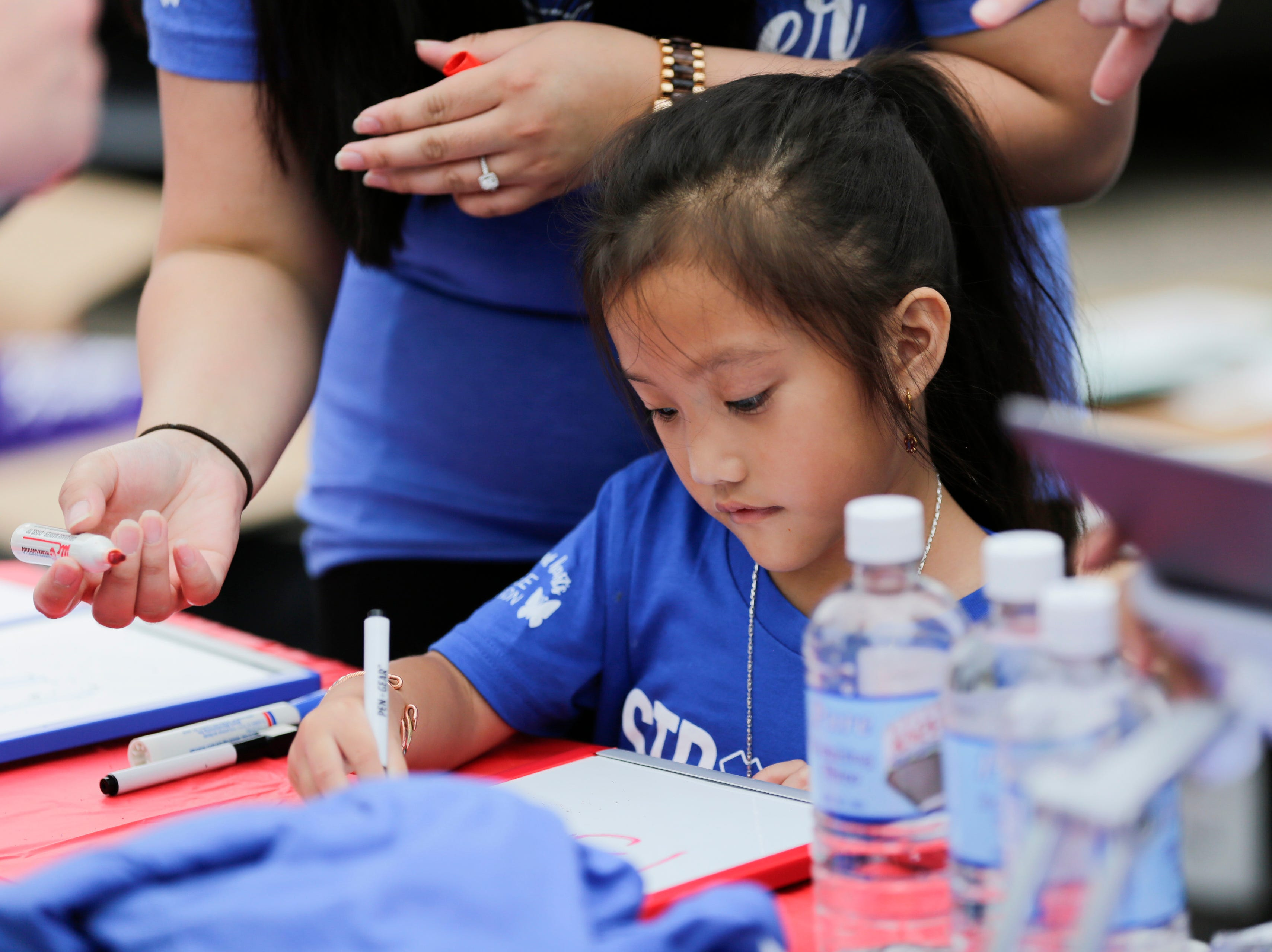 Suabyi Khang, 5, records the number of red shirts that have been sold during the National Night Out event put on by the Wisconsin Rapids Police Department in the Crossview Church parking lot in Wisconsin Rapids Tuesday, August 7, 2018. Red, blue and purple shirts were sold as part of a friendly competition between local law enforcement and fire fighters to raise money for the Fly High Memorial Playground.