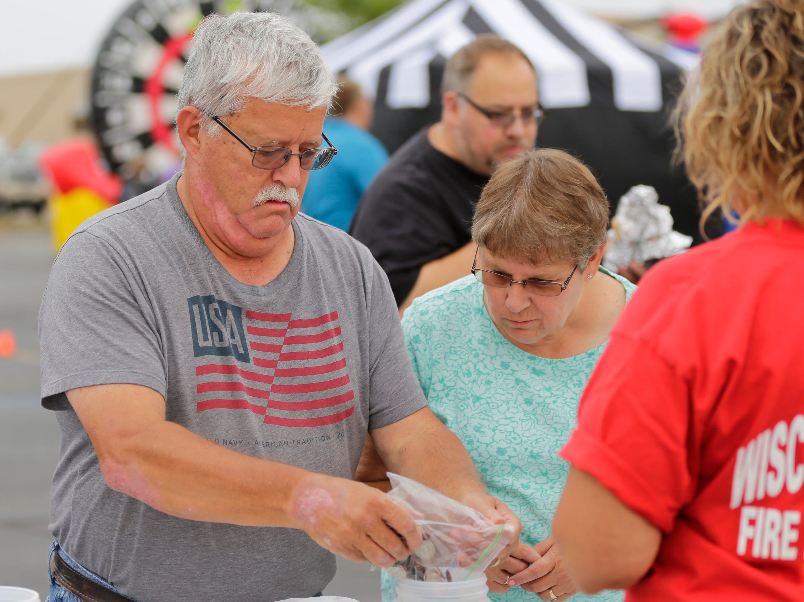 Paul Jeltema donates his change to the penny war during the National Night Out event put on by the Wisconsin Rapids Police Department in the Crossview Church parking lot in Wisconsin Rapids Tuesday, August 7, 2018. Participants in the penny war chose to place their change in a container for the Wisconsin Rapids Police Department, Wisconsin Rapids Fire Department and Wood County Sheriff's Department, raising money for the Fly High Memorial Playground.