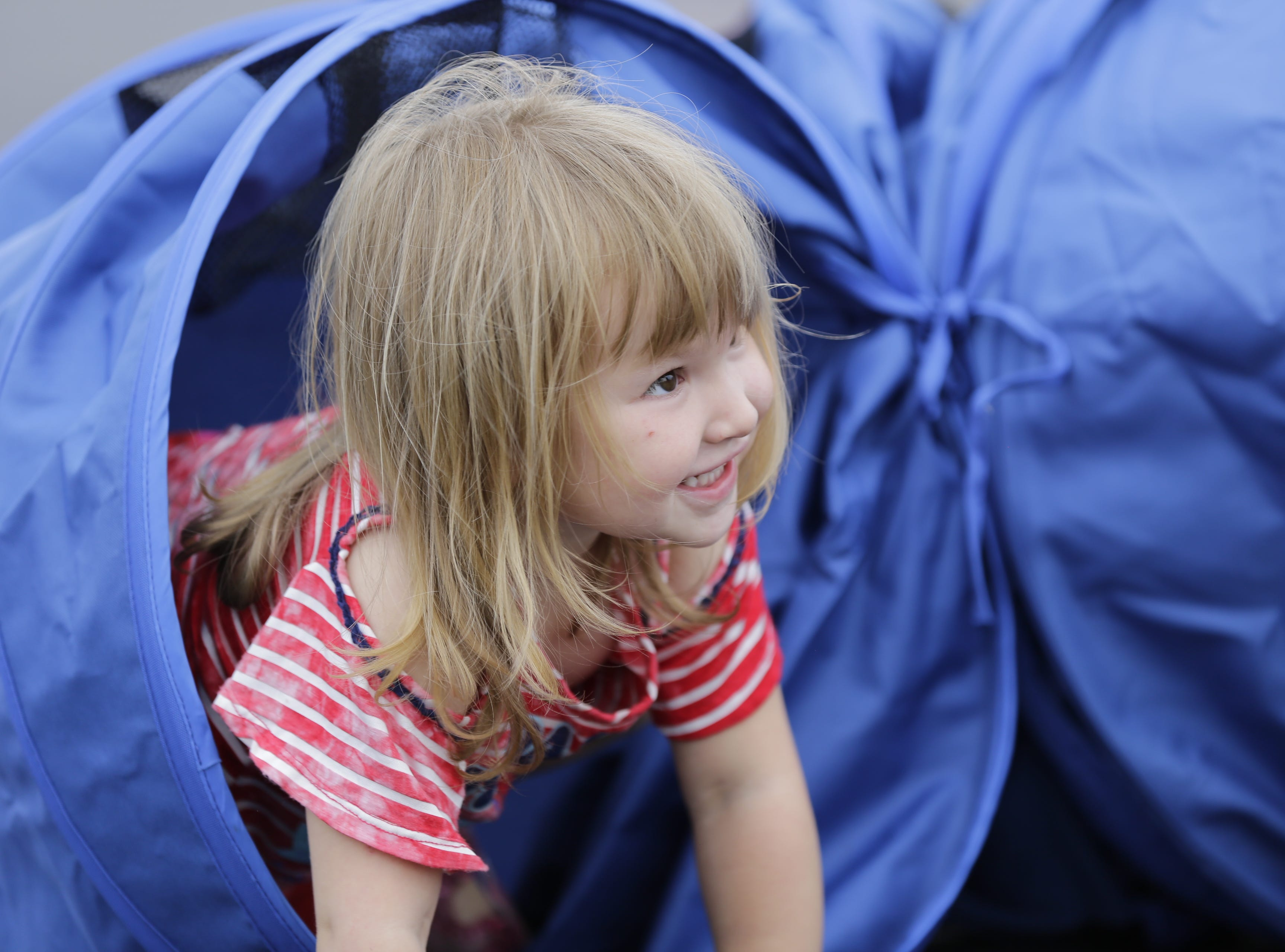 Alyssa Jensen, 2, crawls through a tunnel during the National Night Out event put on by the Wisconsin Rapids Police Department in the Crossview Church parking lot in Wisconsin Rapids Tuesday, August 7, 2018.