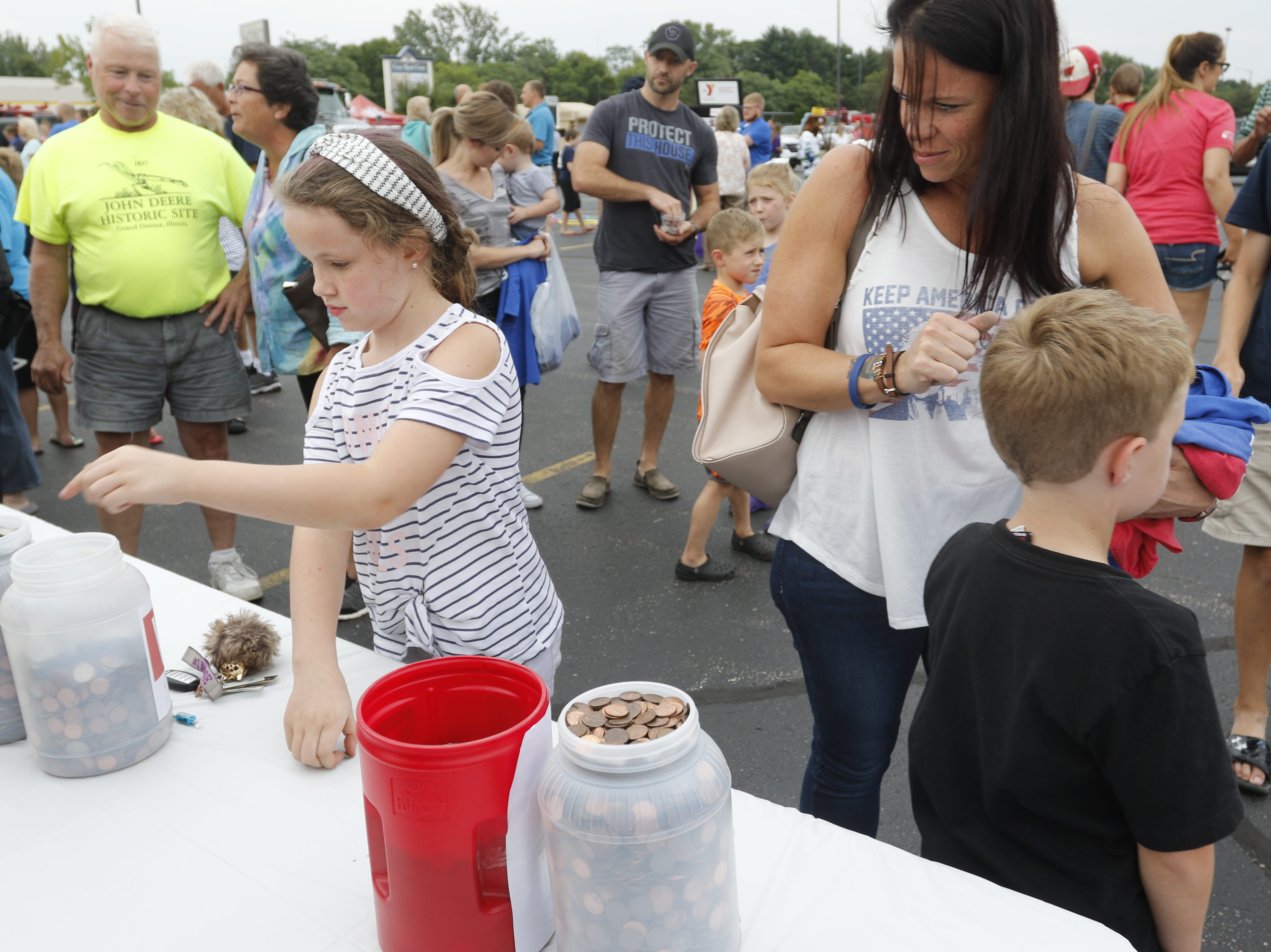 Brylee O'Neil, 8, donates change to the penny war while her mother, Lindsey O'Neil, left, watches, during the National Night Out event put on by the Wisconsin Rapids Police Department in the Crossview Church parking lot in Wisconsin Rapids Tuesday, August 7, 2018.