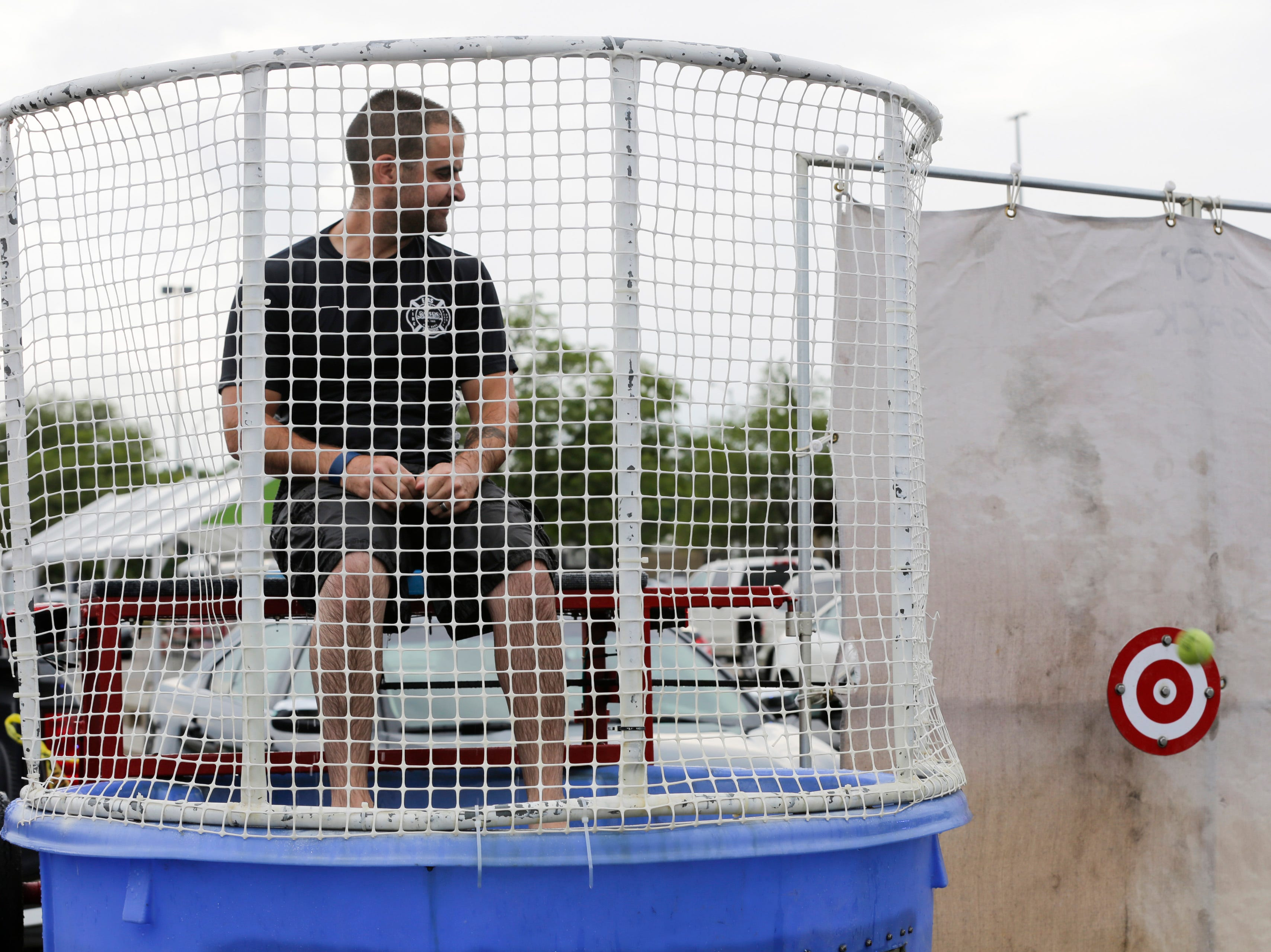 Fire fighter Dustin Lease watches a ball hit the target to send him into the dunk tank during the National Night Out event put on by the Wisconsin Rapids Police Department in the Crossview Church parking lot in Wisconsin Rapids Tuesday, August 7, 2018.