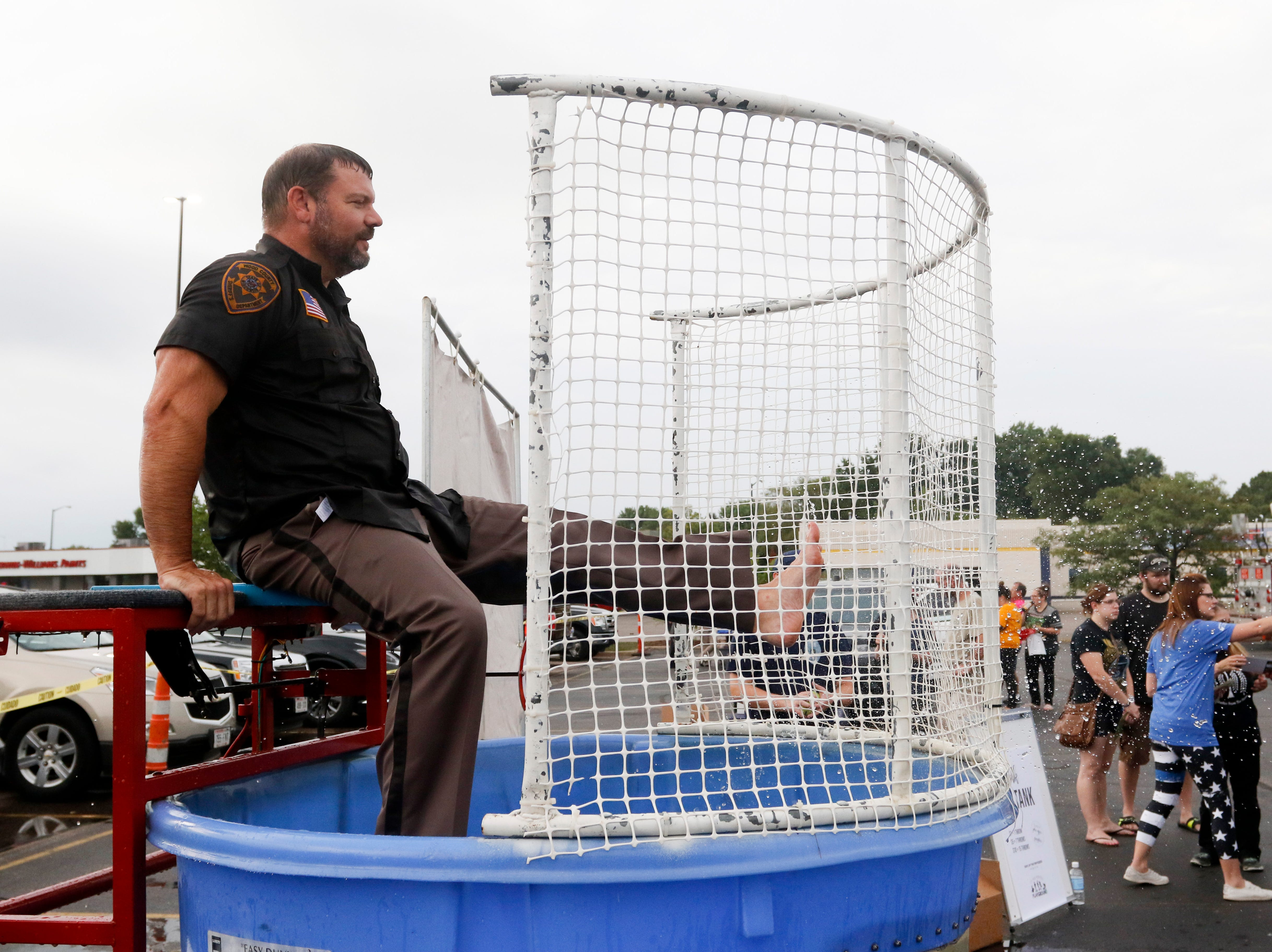 From the dunk tank, Wood County Sheriff's Department Capt. Shawn Becker splashes water at a thrower during the National Night Out event put on by the Wisconsin Rapids Police Department in the Crossview Church parking lot in Wisconsin Rapids Tuesday, August 7, 2018.