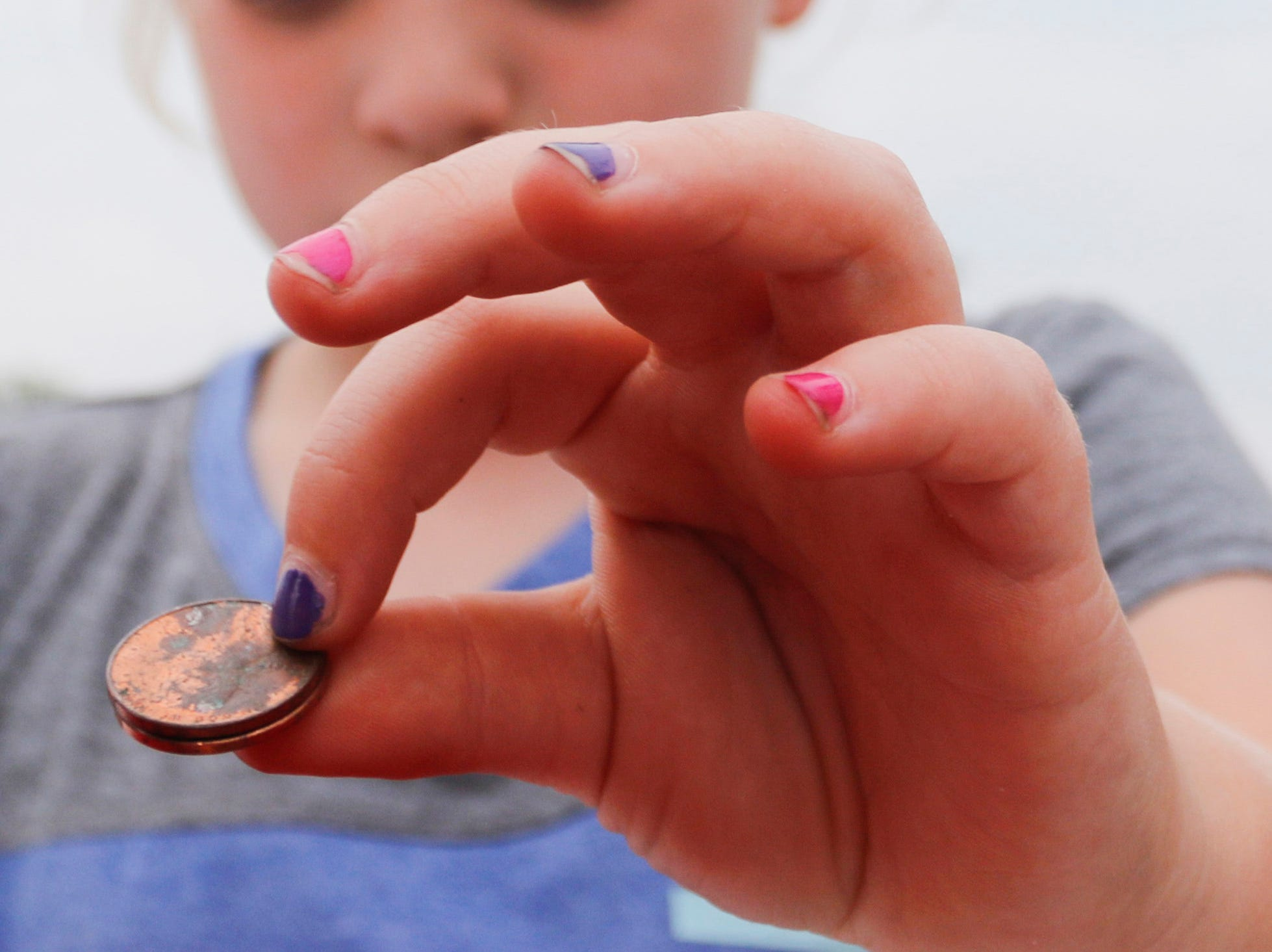 A girl donates pennies to the penny war during the National Night Out event put on by the Wisconsin Rapids Police Department in the Crossview Church parking lot in Wisconsin Rapids Tuesday, August 7, 2018. Participants in the penny war chose to place their change in a container for the Wisconsin Rapids Police Department, Wisconsin Rapids Fire Department and Wood County Sheriff's Department, raising money for the Fly High Memorial Playground.