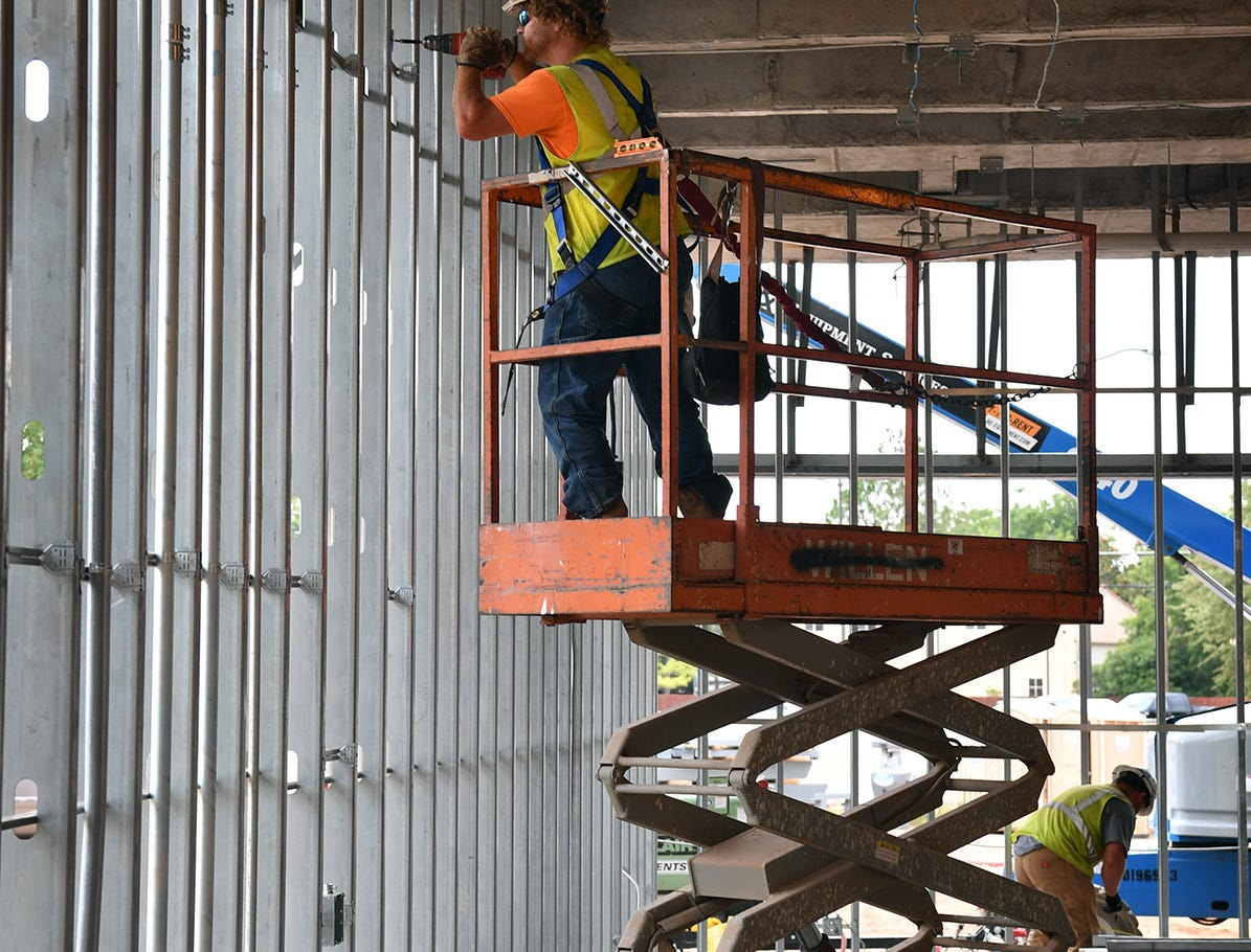 An electrician installs conduit on the first floor of the Midwestern State University Health Sciences and Human Services building under construction.
