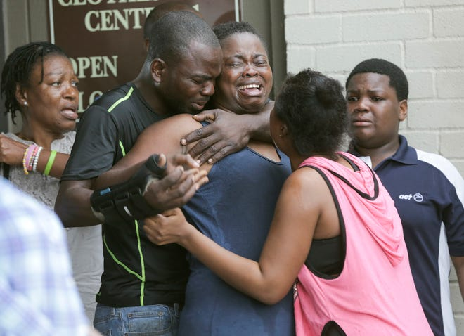 A woman is comforted after the bodies of two children were found stabbed to death in their father's apartment on Saturday, Aug. 4, 2018 in Houston. Authorities say a man suspected of fatally stabbing his two children in Houston has been hospitalized after police found him Sunday with a self-inflicted gunshot wound in his car.