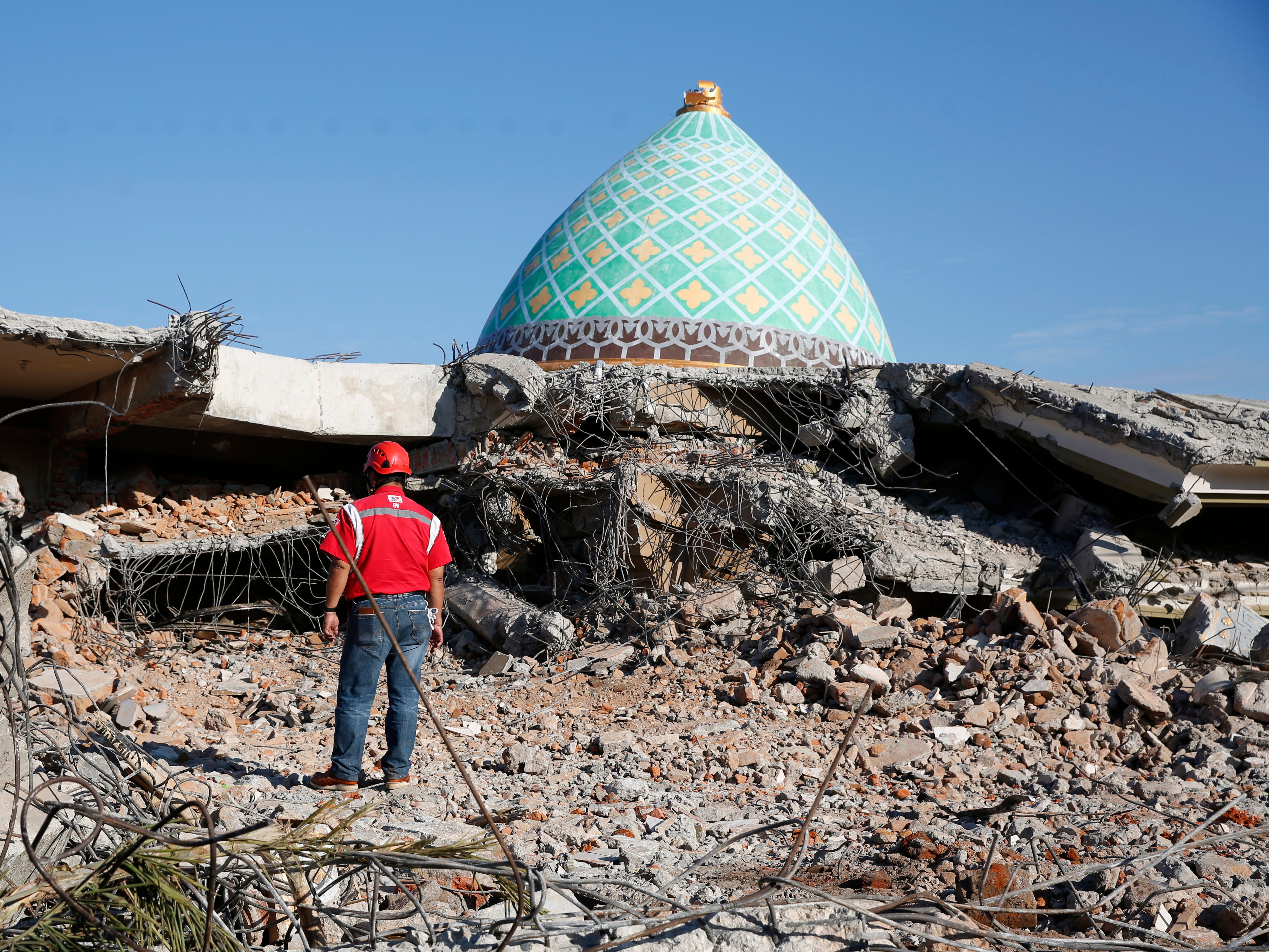 A rescuer stands in front of the roof of a collapsed mosque as he tries to find survivors after an earthquake struck in Tanjung, northern Lombok, West Nusa Tenggara, Indonesia on Aug. 8,  2018.