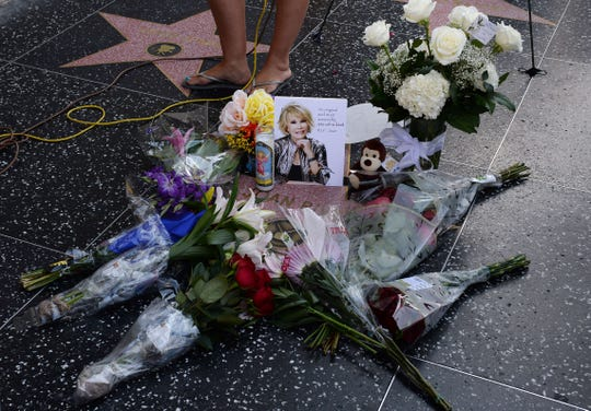Flowers are placed on Joan Rivers' Hollywood Walk of Fame Star in Hollywood, California, on Sept. 4, 2014, following news of the comedian's death in New York at the age of 81.