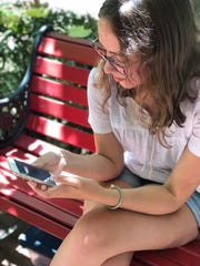 "Lauren Trujillo, 17, texts on her smartphone. She says she and her friends mainly use the newest slang words ""ironically,"" and to joke with one another."