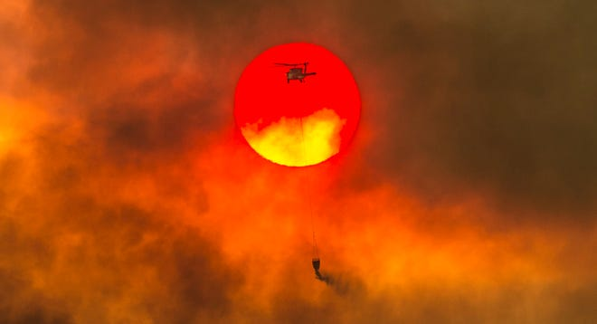In this Friday, July 27, 2018, photo, a firefighting helicopter makes a water drop as the sun sets over a ridge burning near Redding, Calif., in efforts against the Carr Fire. Scorching heat, winds and dry conditions complicated firefighting efforts.