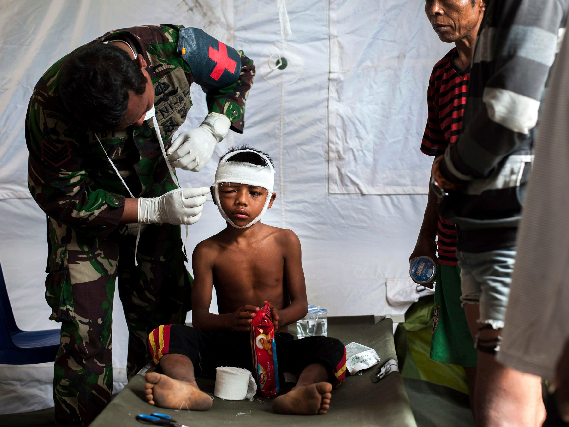 A military paramedic tends to a boy who suffers head injury from Sunday's earthquake at a makeshift hospital in Kayangan, Lombok Island, Indonesia on Weds. Aug. 8, 2018.