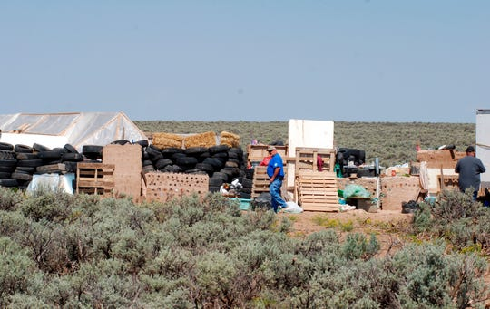 Taos County Solid Waste Department Director Edward Martinez, center, surveys property conditions at a disheveled living compound at Amalia, N.M., on Aug. 7. A New Mexico sheriff said searchers have found the remains of a boy at the makeshift compound that was raided in search of a missing Georgia child.