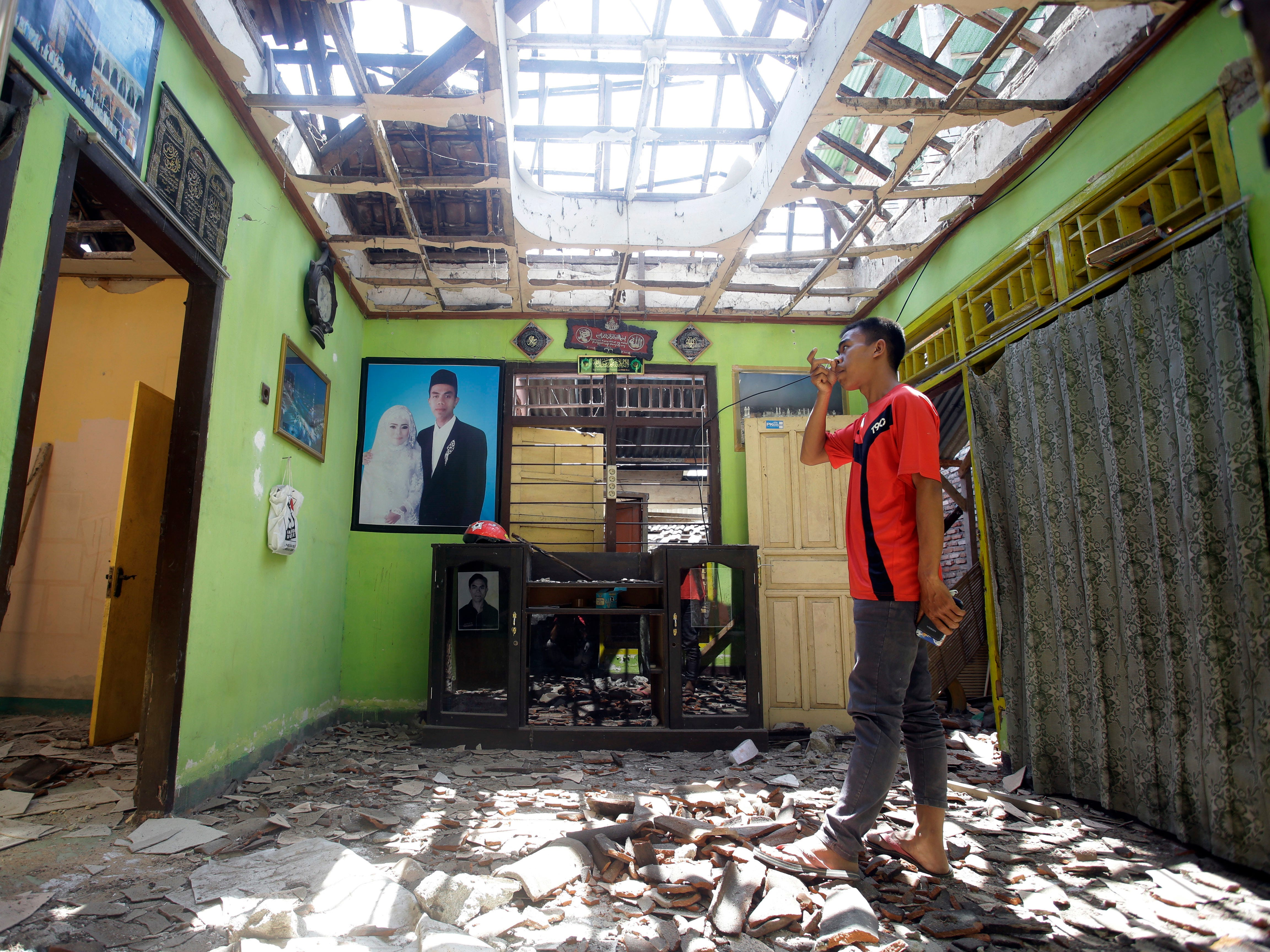 A villager visits his damaged house in the Kekait village affected by Sunday's earthquake in North Lombok, Indonesia on Weds. Aug. 8, 2018. Aid has begun reaching isolated areas of the Indonesian island struggling after an earthquake killed over 100 people as rescuers intensify efforts to find those buried in the rubble.