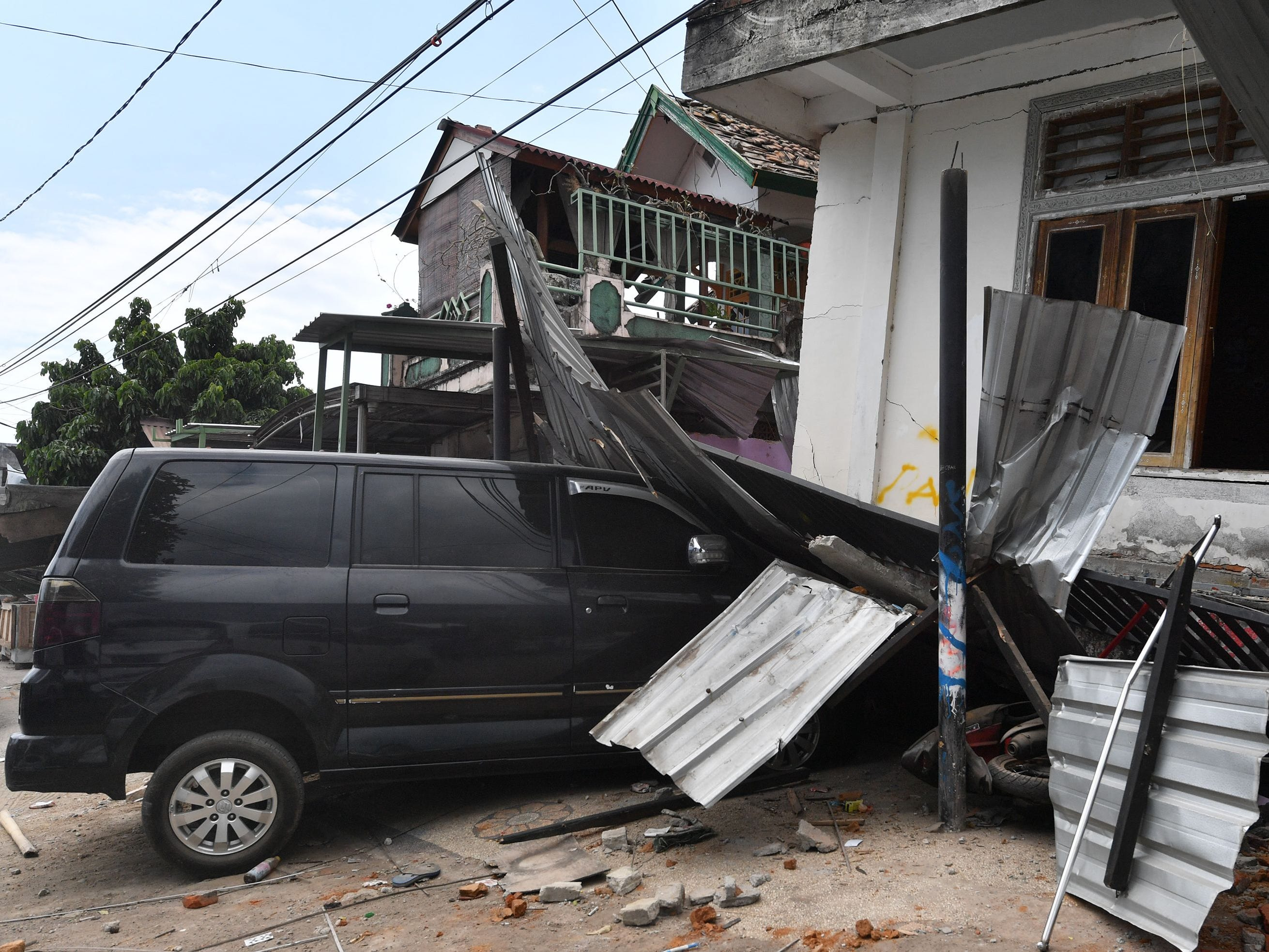 A damaged car and houses are seen in Bangsal, northern Lombok on Aug. 8, 2018, three days after the area was struck by an earthquake.