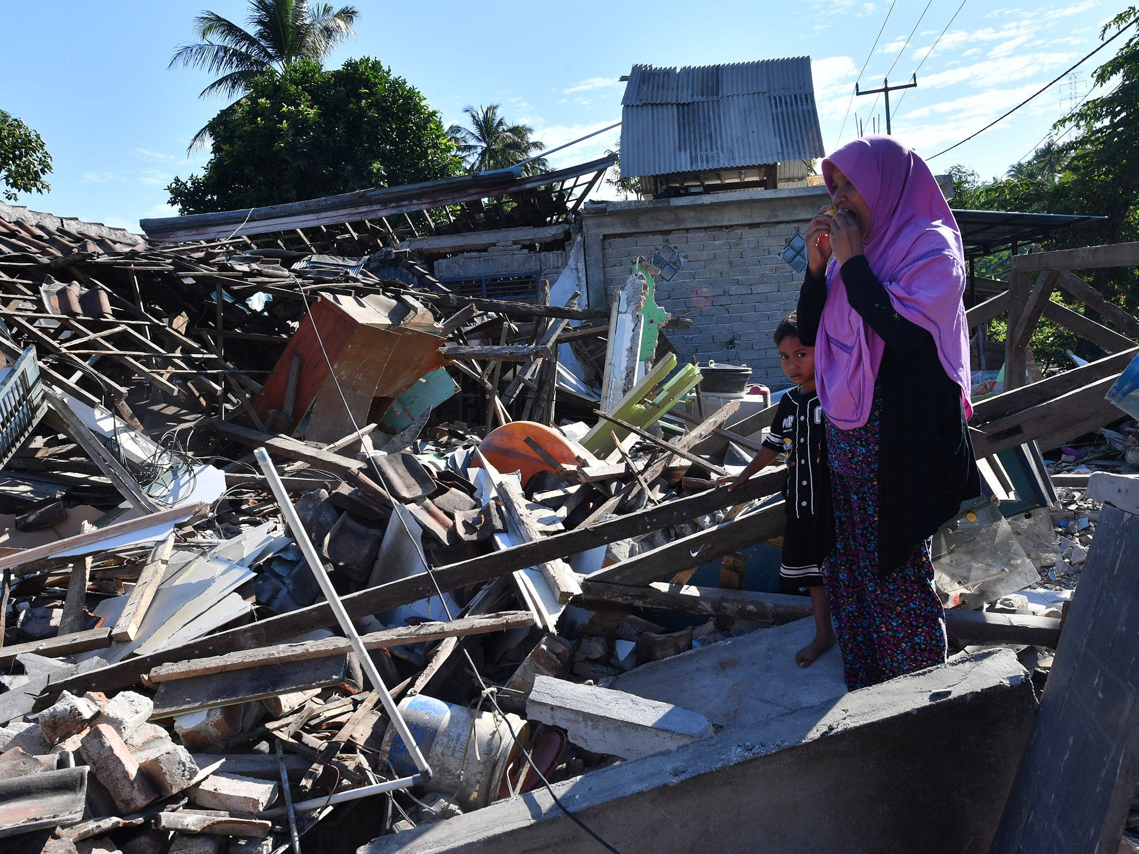A woman and boy watch as men clear the wreckage of houses damaged by an earthquake in Menggala, North Lombok on Aug. 8, 2018, three days after the earthquake struck the area.