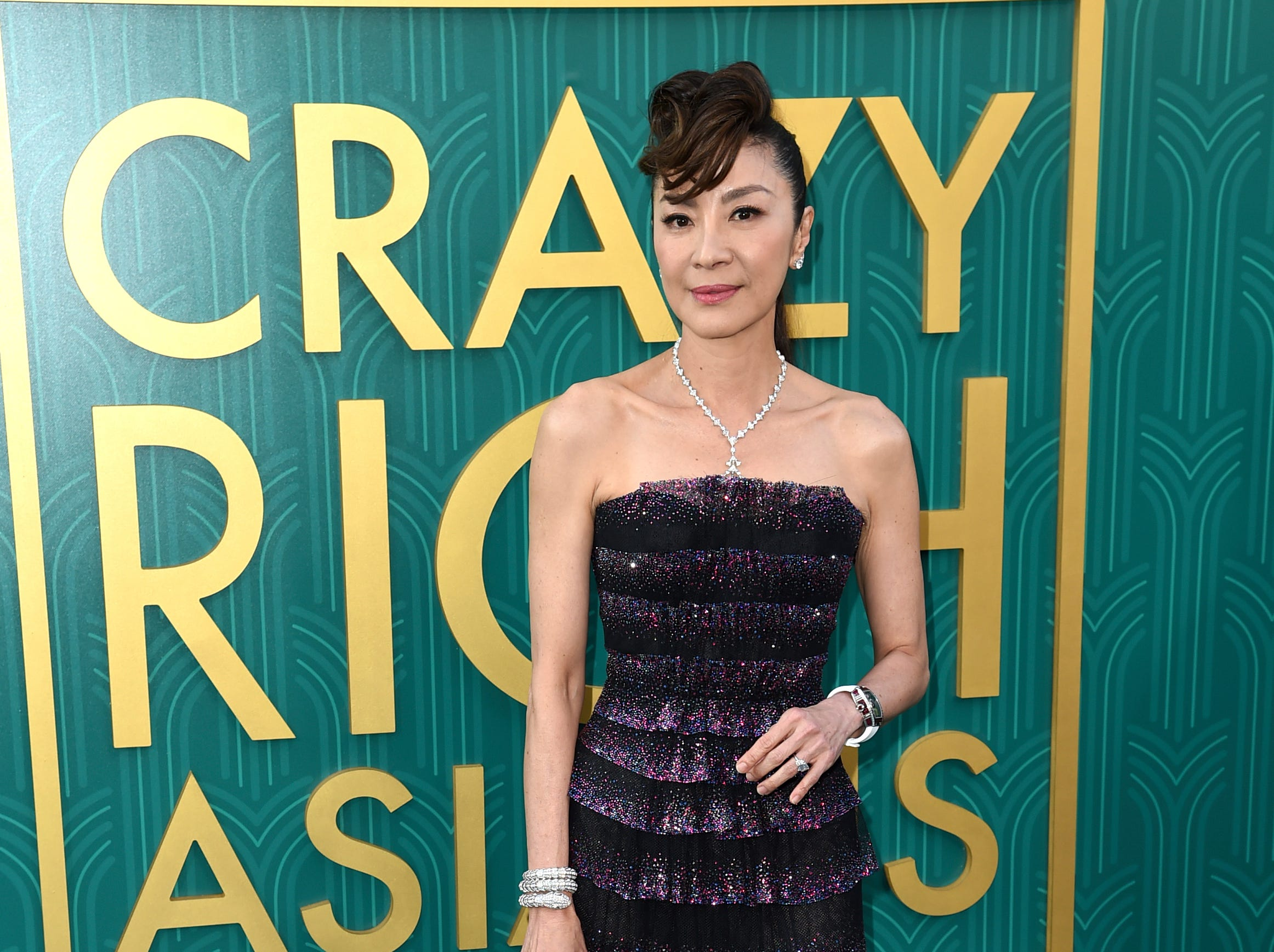 "Michelle Yeoh wore a black tiered gown at the premiere of ""Crazy Rich Asians."" She play Nick's mother, Eleanor Sung-Young."