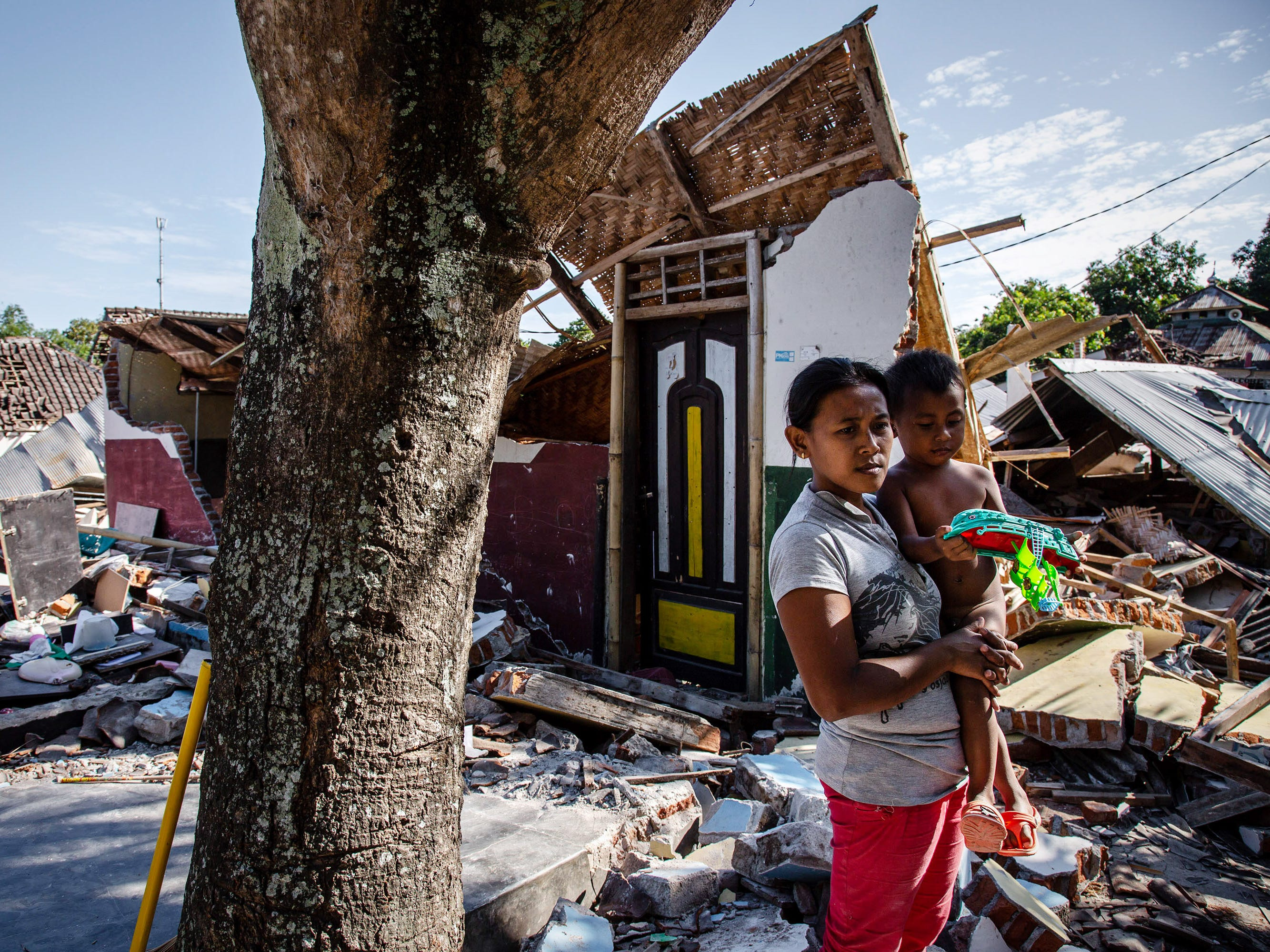 A woman with her son stands near the ruins of their houses following an earthquake in Pemenang on Aug. 8, 2018 in Lombok Island, Indonesia.