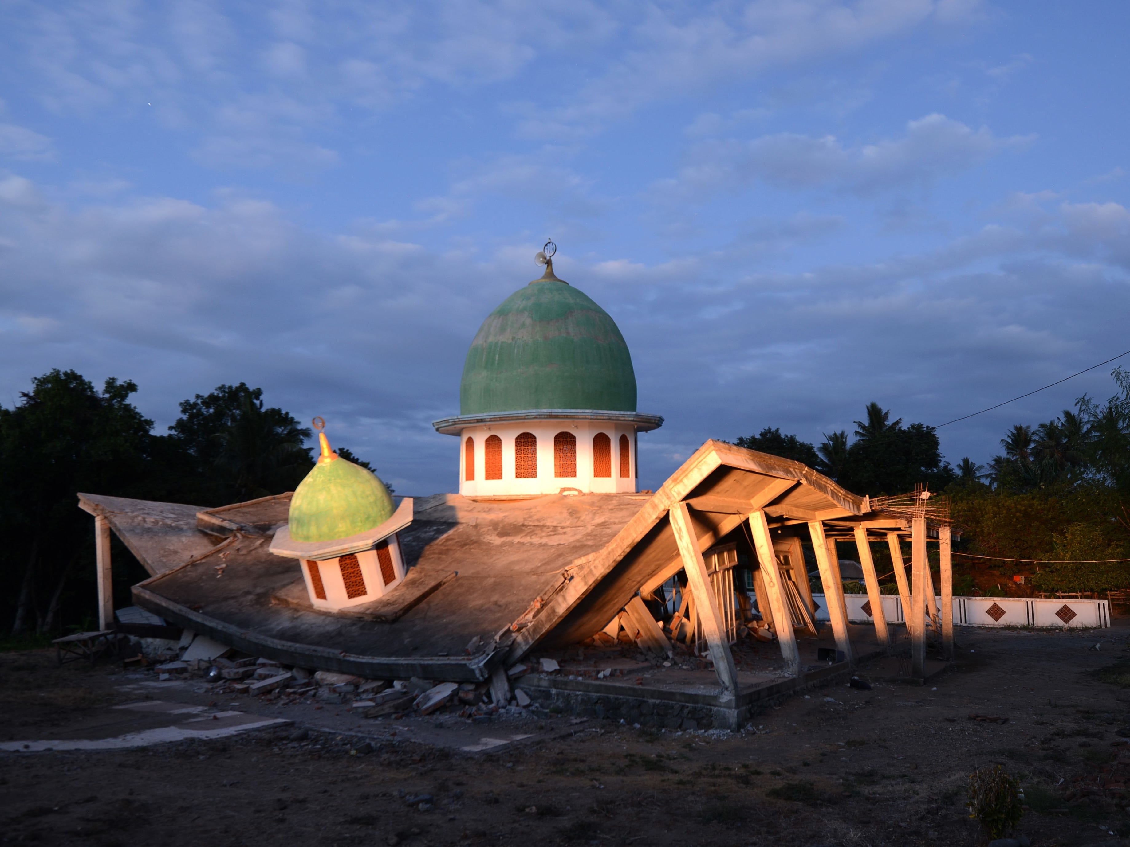 A collapsed mosque is seen as the sun set at Kayangan subdistrict in North Lombok on West Nusa Tenggara province on August 8, 2018, three days after an earthquake hit the area.