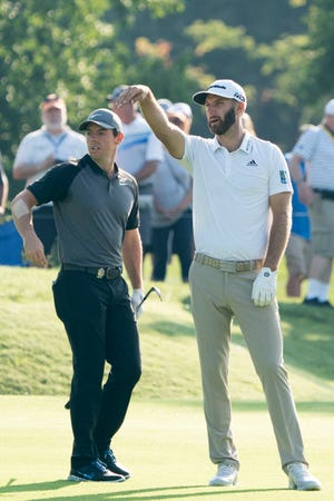 Rory McIlroy and Dustin Johnson stand on the seventh fairway during the Wednesday practice round of the PGA Championship golf tournament at Bellerive Country Club.