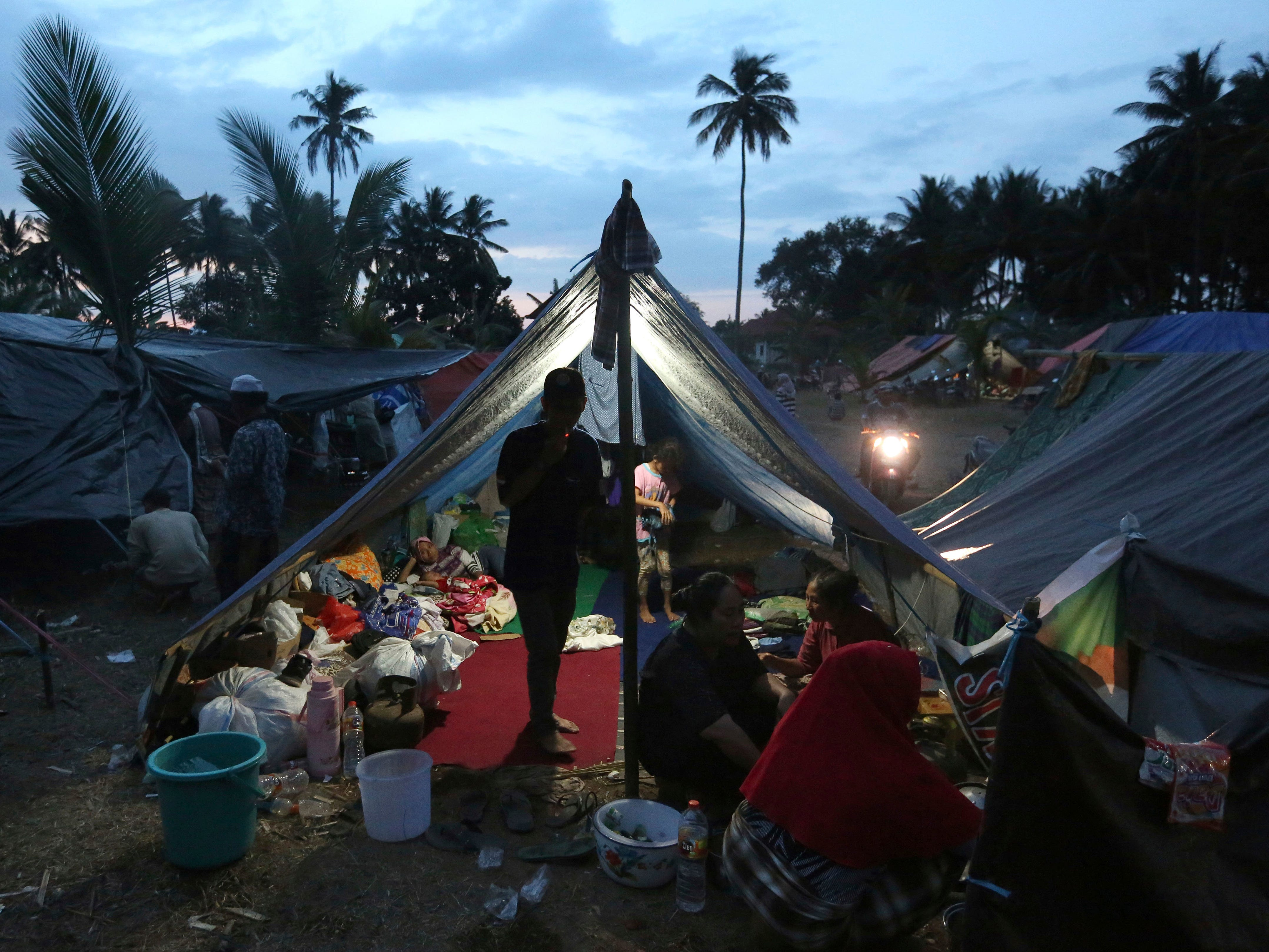 Villagers gather at a temporary shelter after fleeing their damaged village affected by Sunday's earthquake in North Lombok, Indonesia on Weds, Aug. 8, 2018. Aid has begun reaching isolated areas of the Indonesian island struggling after an earthquake killed over 100 people as rescuers intensify efforts to find those buried in the rubble.