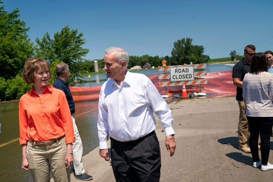 Minnesota Gov. Mark Dayton, center, and Sen. Tina Smith, left, observe flooding in Currie, Minn., July 6, 2018.