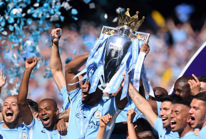 Manchester City players celebrate their 2017-18 title with the Premier League trophy.
