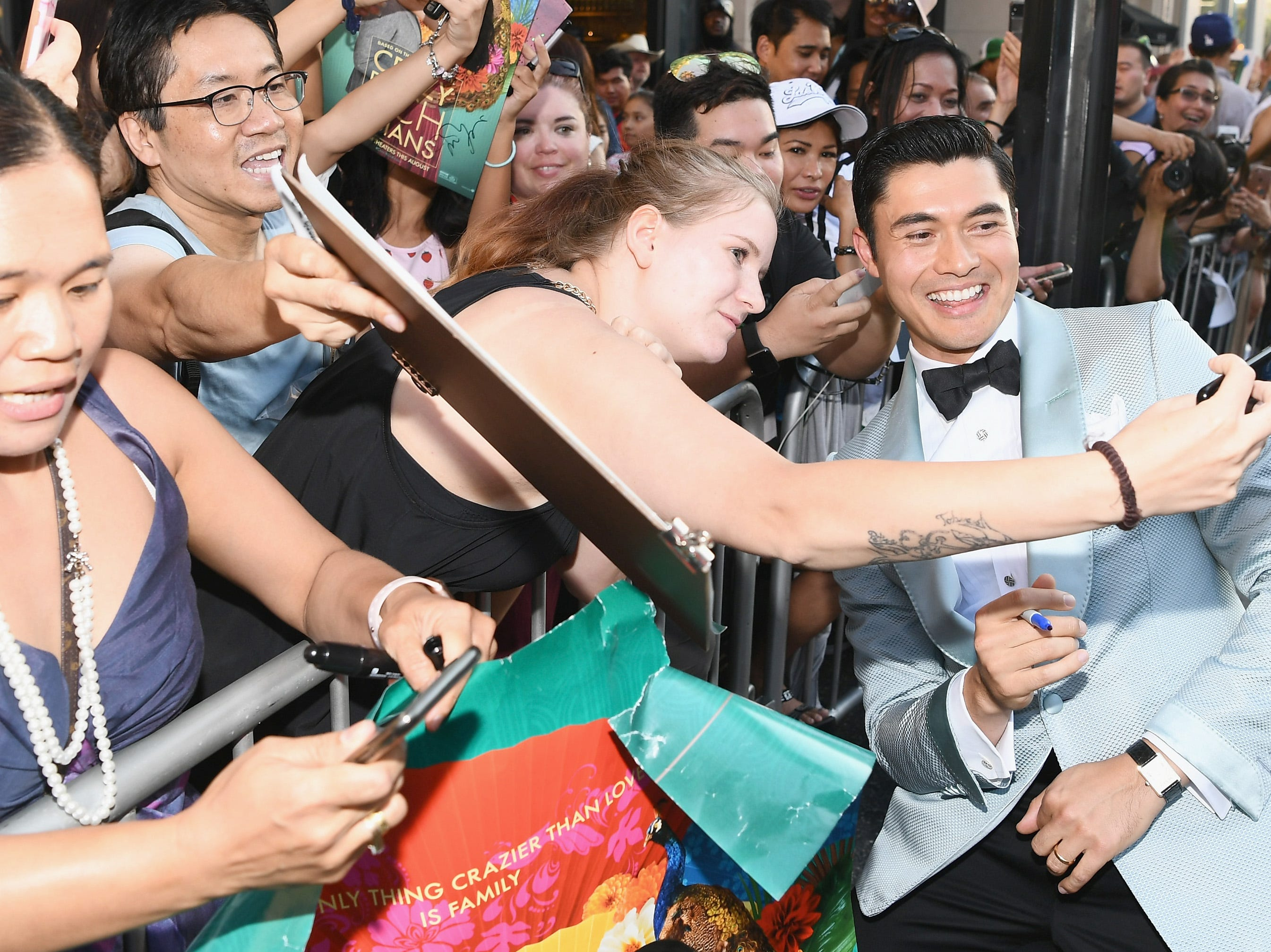 "Henry Golding took pictures with fans at the ""Crazy Rich Asians"" premiere."