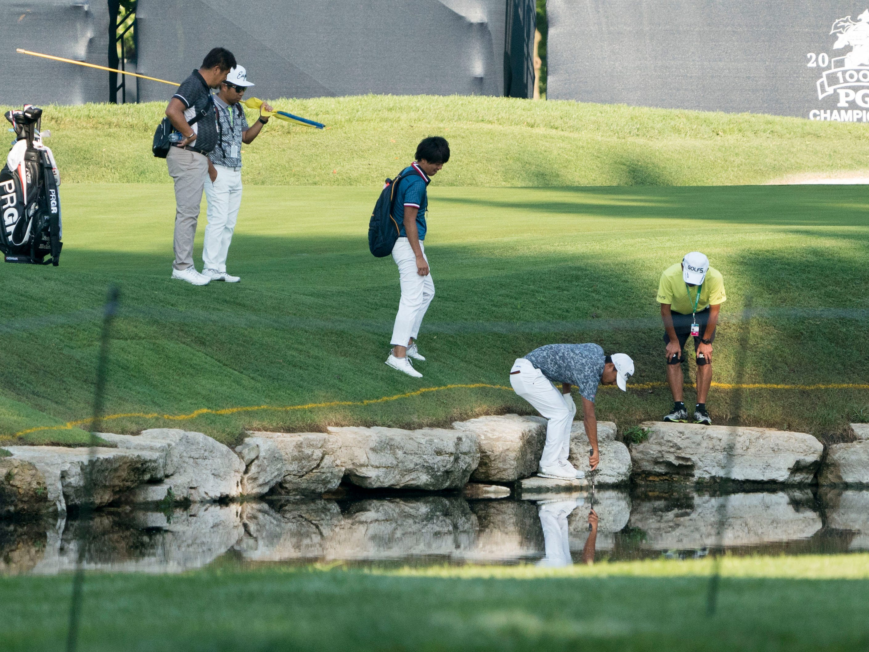 Satoshi Kodaira reaches for his golf ball in the water on the sixth hole.