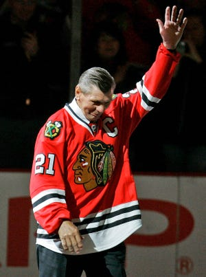 Chicago Blackhawks great Stan Mikita waves to fans as they as he is introduced before an NHL hockey game against the San Jose Sharks in Chicago.