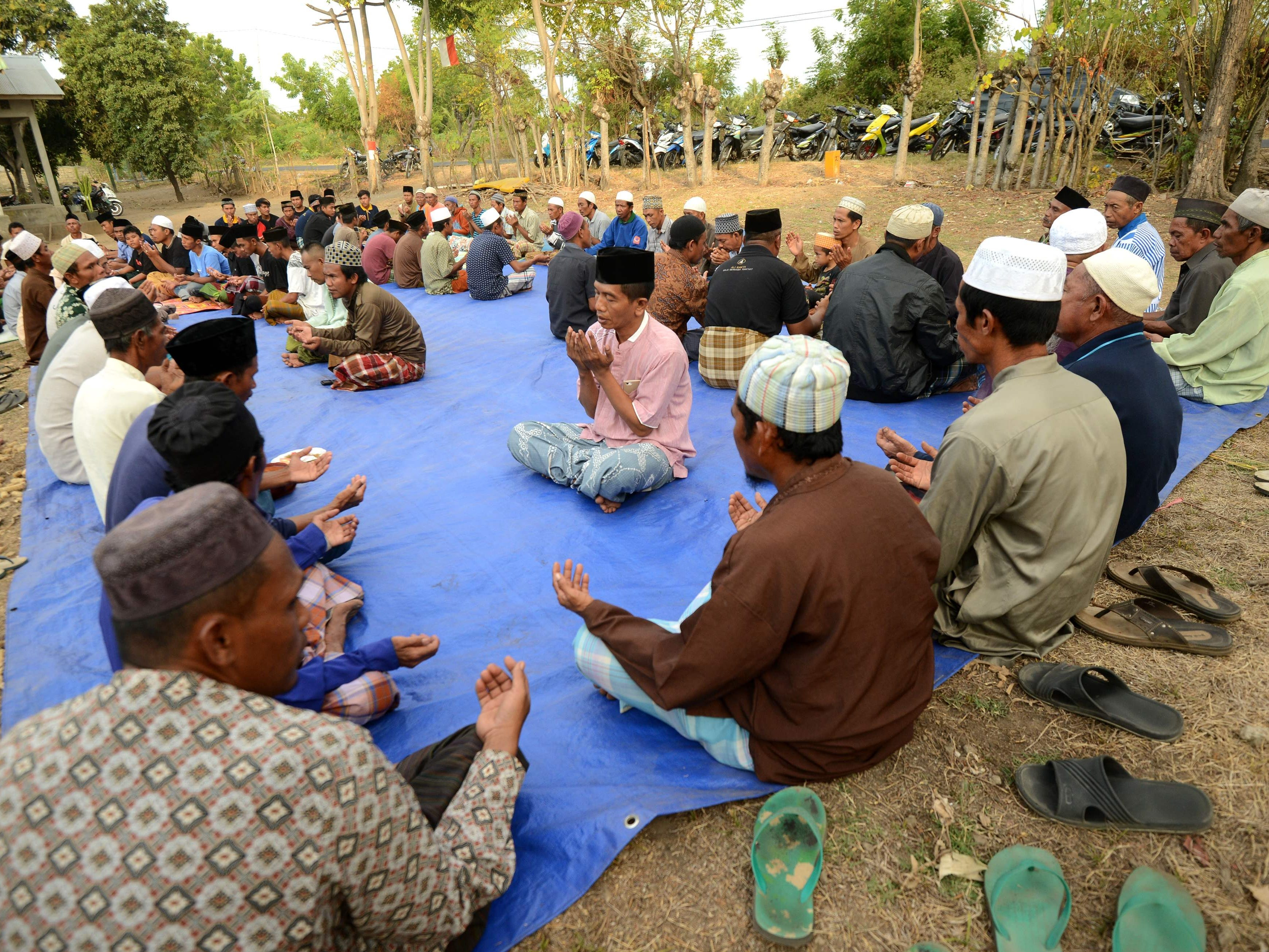 Villagers pray for their family victims at Kayangan subdistrict in North Lombok on West Nusa Tenggara province on Aug. 8, 2018, three days after an earthquake hit the area.