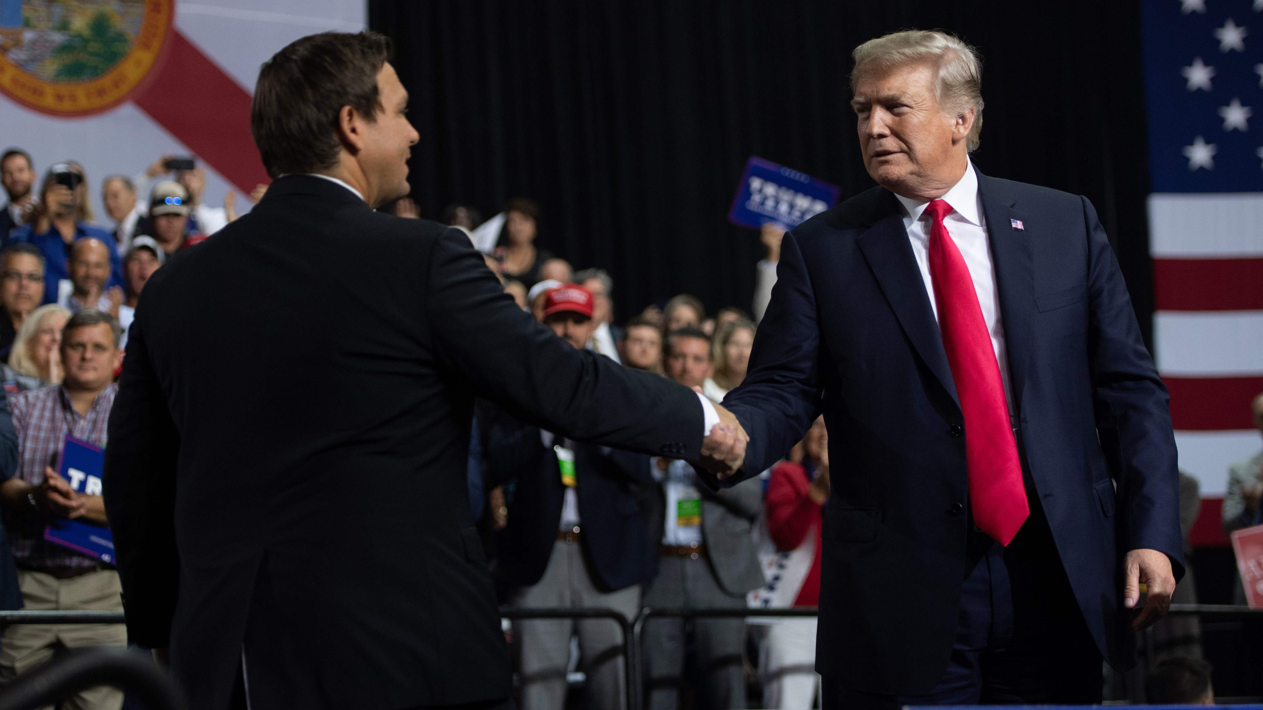 President Donald Trump shakes hands with US Representative Ron DeSantis, Republican of Florida, and candidate for Florida Governor, as he speaks during a campaign rally at Florida State Fairgrounds Expo Hall in Tampa, Fla. on July 31, 2018.