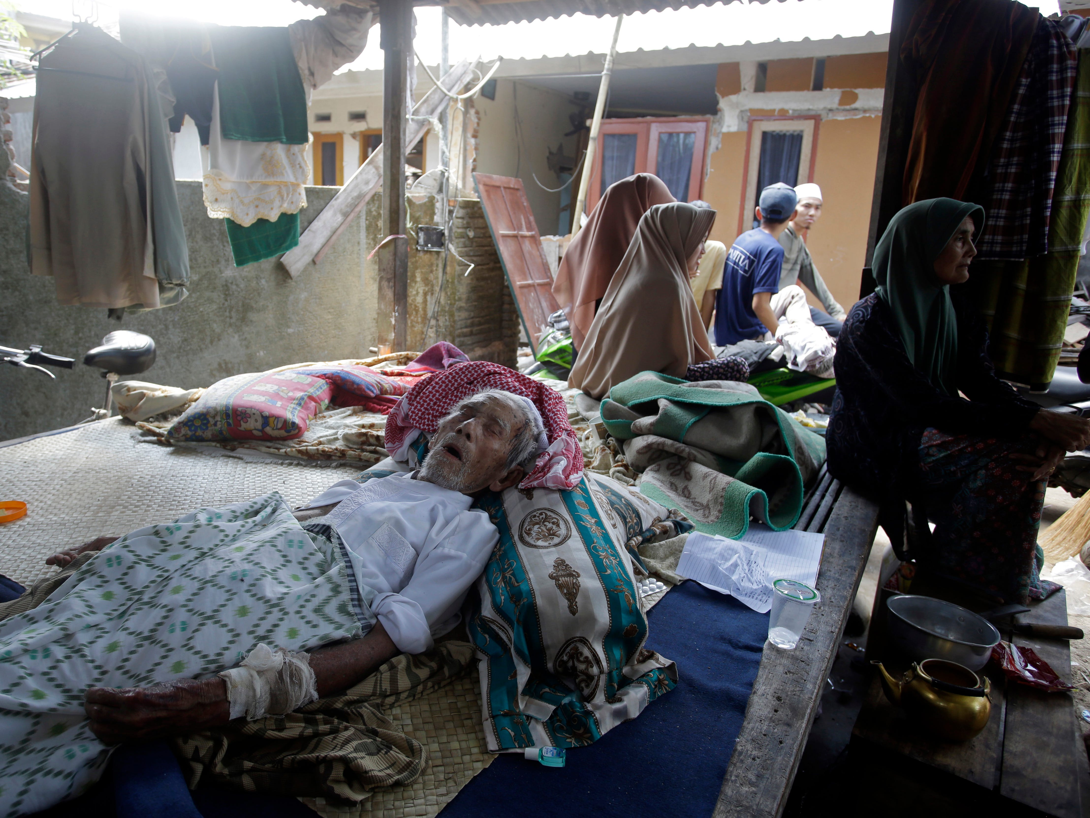 An elderly man injured in an earthquake lies at a temporary shelter in the Kekait village affected by Sunday's earthquake in North Lombok, Indonesia on Weds. Aug. 8, 2018. Aid has begun reaching isolated areas of the Indonesian island struggling after an earthquake killed over 100 people as rescuers intensify efforts to find those buried in the rubble.
