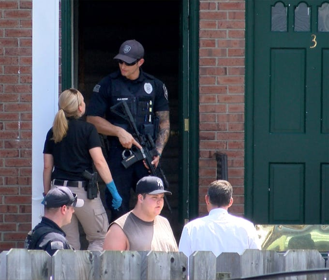A Keyport police officer stands in the doorway of a  Center Street apartment building Thursday afternoon, August 9, 2018, where a man was apparently shot.