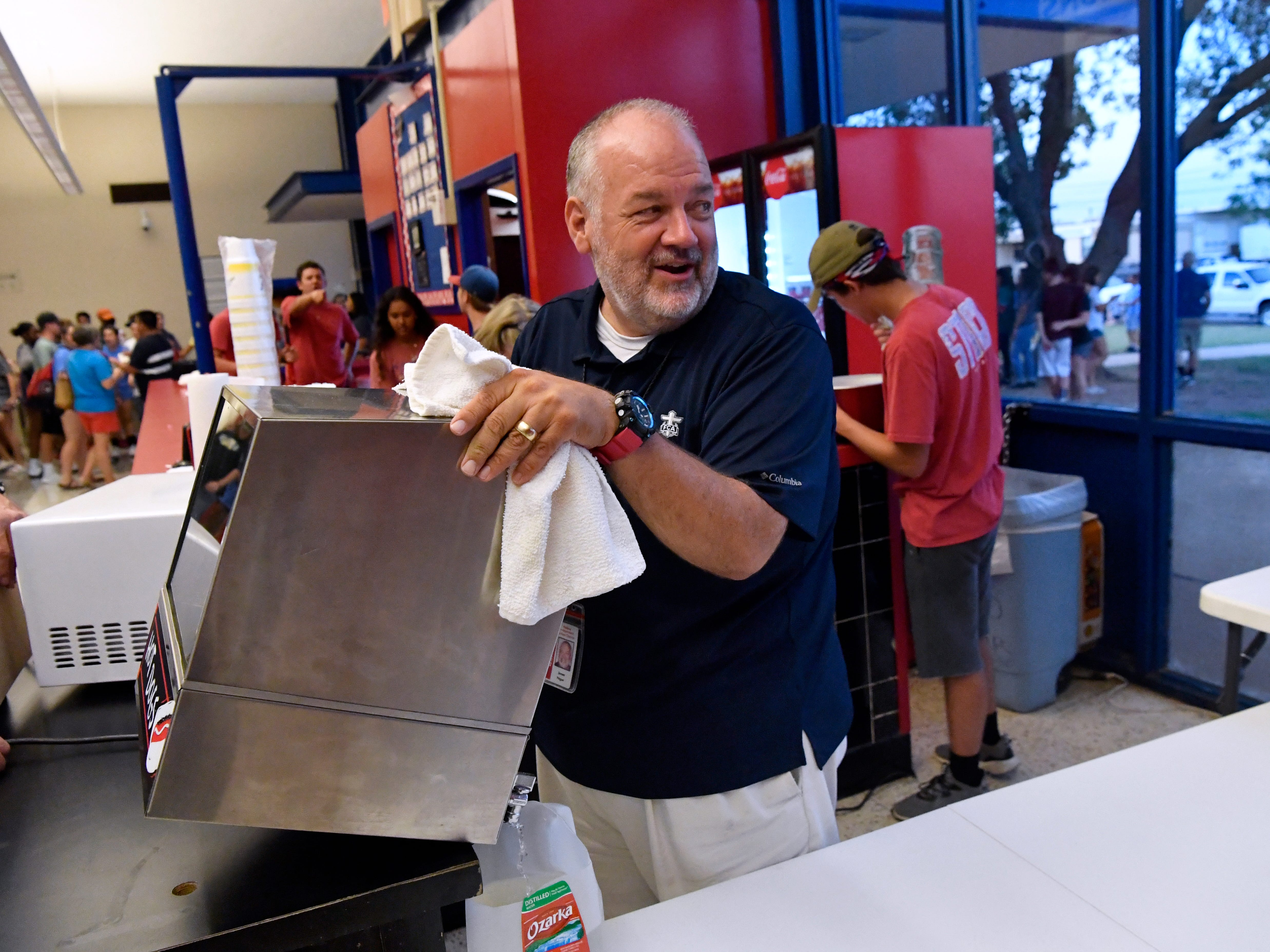 Jimmy Pogue says goodbye to a friend as he cleans out the hotdog box at the Cooper High School gymnasium's concession stand August 7, 2018.