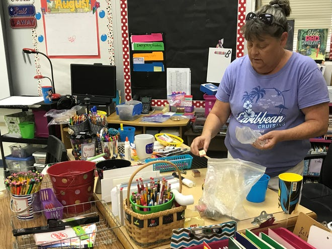 Abby Brown, a fourth-grade teacher at the Abilene Independent School District's Dyess Elementary, organizes her stamp collection on her desk Thursday. Dyess is one of three elementary schools that a committee is recommending be replaced if the district calls a bond election.