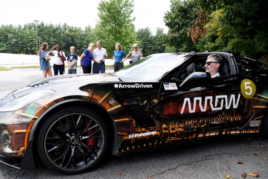 Friends and family wait to watch Paul Endry drive the Arrow Electronics Semi-Autonomous Motorcar Tuesday. Endry, an Asheville optometrist, was paralyzed in a cycling accident last year. The vehicle accelerates and brakes with a sip-and-puff device while sensors mounted to sunglasses allow head tilting motions to steer.