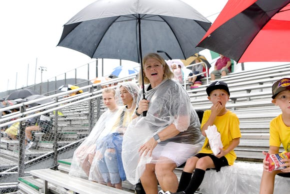 Kelly Gentry, wife of Murphy football coach David Gentry, braves the rain as she stands up at her seat in the bleachers to cheer on the Bulldogs during the Reynolds Football Jamboree at Reynolds High School on Wednesday, Aug. 8, 2018.