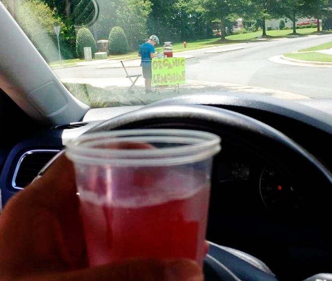This Aug. 4, 2018, photo provided by James Castellano, of Monroe, N.C., shows a drink he bought from a boy, background, in Monroe. Deputies in North Carolina have arrested a suspect who they say robbed the 9-year-old lemonade vendor of $17 at gunpoint, an incident which led to more than $200 in donations and a riding lawn mower, Tony Underwood of the Union County Sheriff's Office said Wednesday.