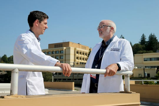 Harrison's residency program got underway this summer. Resident MD Jacob Van Fleet, left, who was born at the Naval Hospital in Bremerton, by doctor Ronald Dommermuth, right, who is now one of his instructors. Harrison Medical Center in Bremerton is behind them.